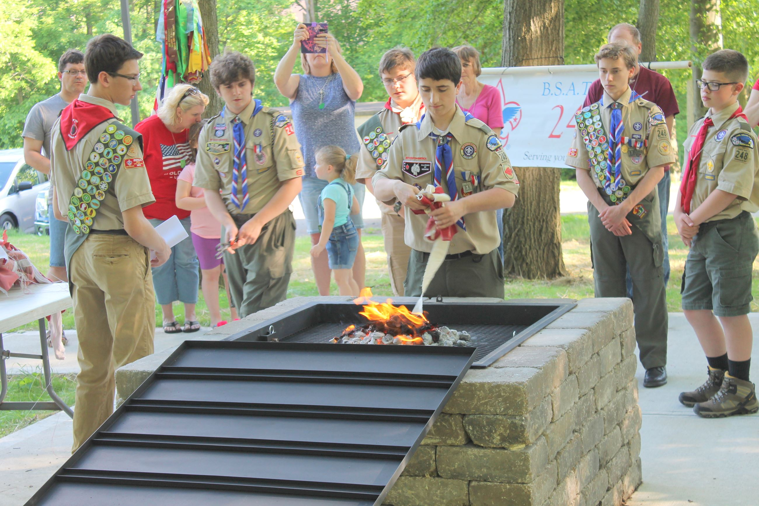Scout places flag in fire