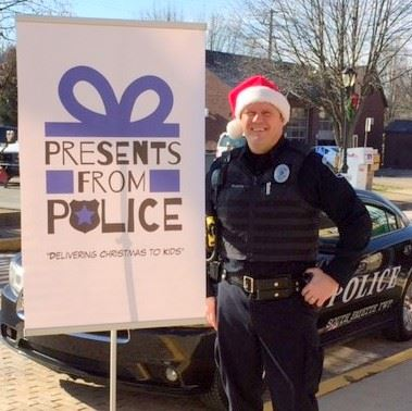 Officer Mike Kuchta wears a Santa hat with a Presents from Police sign