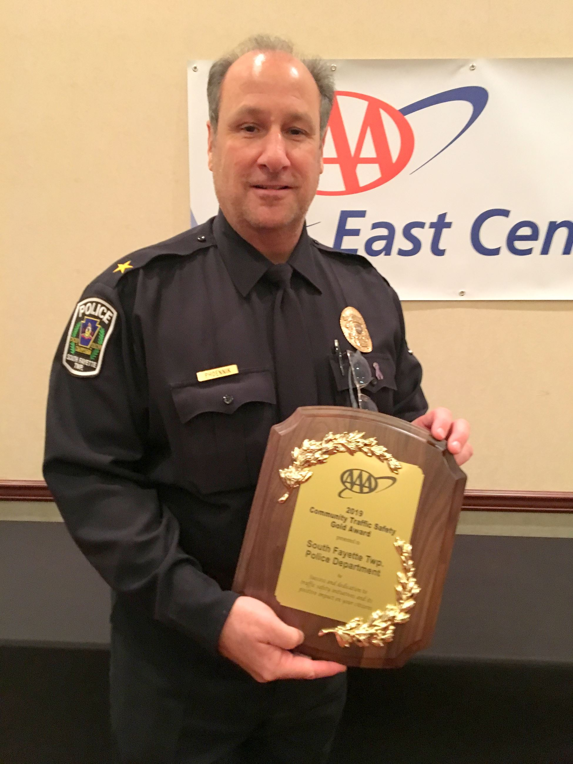 Police Chief John Phoennik holds AAA plaque for traffic safety award