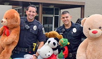 Officers hold donated teddy bears